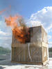 Flames coming out of the first doorway of a test structure after the floor has collapsed into the basement.