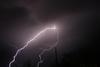 Photo of purplish black sky with a streak of bright lightning