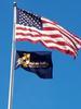 Baldrige program flag and American flag waving on steel pole against blue sky