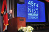 Under Secretary of Commerce for Standards and Technology and NIST Director Walter G. Copan at a podium in front of a screen showing the words 45th Annual NIST Awards Ceremony.