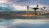 Flying drone over water with mountain landscape in the background