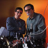 David Wineland and Dietrich Leibfried wear goggles and stand in front of equipment
