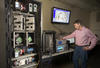 NIST engineer Rick Candell is seen monitoring the strength and clarity of a wireless signal run through a virtual factory environment (a graphic of which is seen on a monitor above Candell's head).
