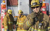 firefighter speaks into a handheld radio
