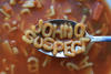 A spoon hovers above a bowl of alphabet soup. On the spoon are the letters JOHN Q SUSPECT.