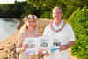 Newly wed examiners Kay Kendall and Glenn Bodinson pose together in Hawaiian dress holding Baldrige booklets on a tropical beach