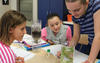 Pewaukee School District Measure What You Treasure blog photo showing three middle school female student doing a science experiment with a two liter plastic bottle.