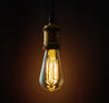 An old-fashioned Edison lightbulb hangs from a wire.