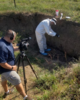 FBI Gelogist-Forensic Examiner and videographer in a soil pit.