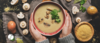 woman in a grey sweater holding a bowl of cream of mushroom soup