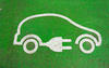 electric vehicle symbol of a car with a plug attached on a green background