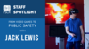 "This image shows the text ""PSCR Staff Spotlight: From Video Games to Public Safety with Jack Lewis"" next to an image of a young man wearing a VR headset, with a T.V. screen depicting a fire behind him"