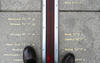 pair of feet standing on either side of the prime meridian in Greenwich, England