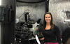 Callie Higgins in a lab. She is standing in front of a reflective screen surrounding an atomic force microscope.